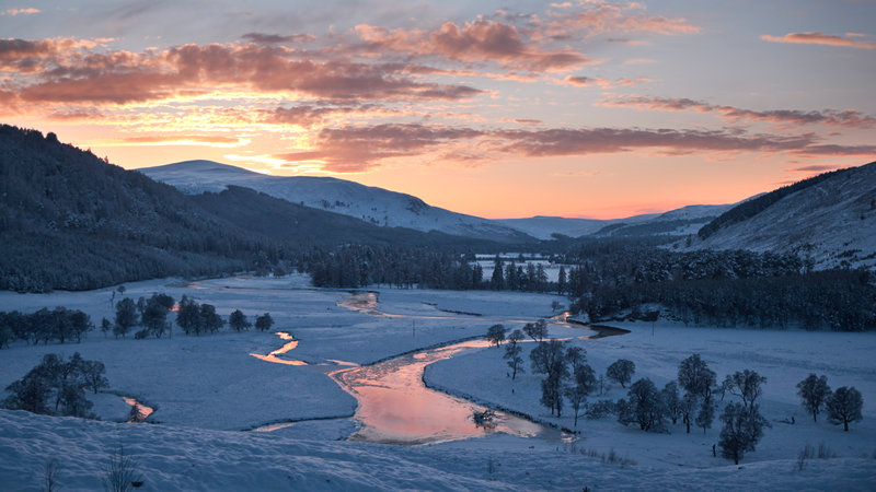 Cairngorms national park is in the mountains of the Scottish highlands. View over a river valley in snow at sunset.