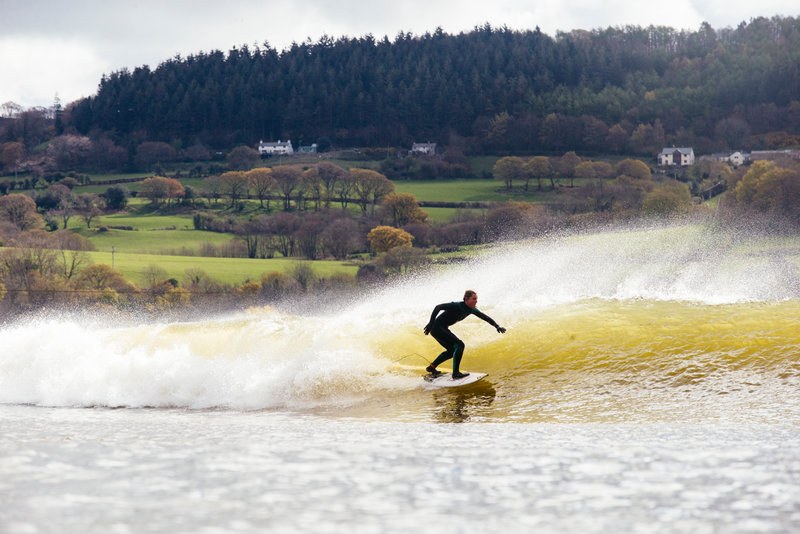 Surfer riding a wave at the WaveGarden artificial wave lagoon, Conwy Valley in the lee of the Snowdonia, Wales.