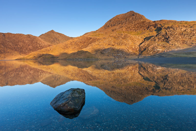 First light on the slopes of Mount Snowdon. Reflections of the landscape in the flat calm waters of a mountain laken. Dawn light.